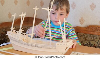 sitting boy attaching mast with flag to toy model of ship