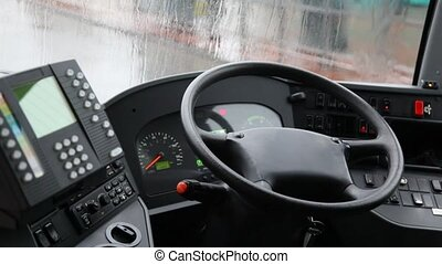 empty cab of  bus shown from inside, rain behind  window