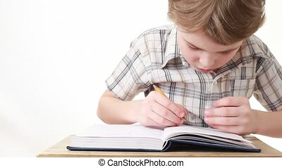 sitting boy writing on notebook on white background