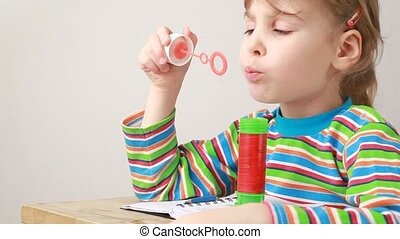 little girl sitting at table, blowing soap bubbles and...