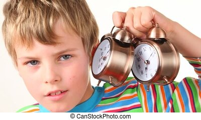 boy holding pair of ringing alarm clocks near his ear