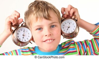 boy holds pair of alarm clocks near his ears - smiling boy...