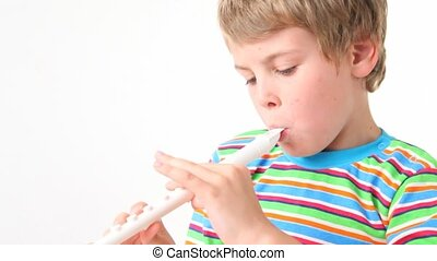 portrait of boy plays on wooden pipe on white background