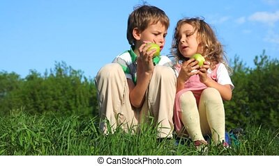 brother and sister sitting on grass, eating apples in park