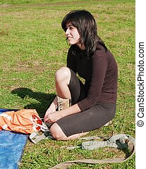 The girl in brown clothes sits on a green grass on airfield