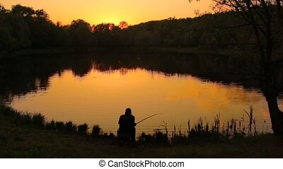 back view of fisherman catching fish at pond during sunset
