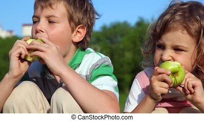 boy with girl sitting and eating apples outdoor