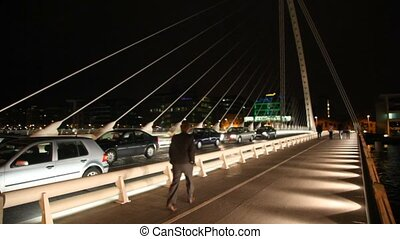 cars stoped, people walk at night Samuel Beckett Bridge,...