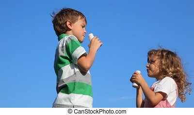 boy with girl standing and drink yoghurt