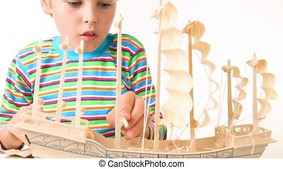 boy with interest constructing toy model of ship on white...