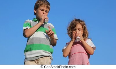 boy with girl drink yoghurt and against blue sky