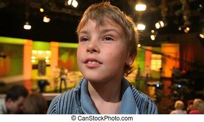 portrait of boy looking around in TV studio - portrait of...