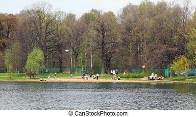people have a rest on coast of spring park near lake