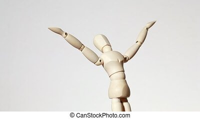 rotating wooden figure of man with raised hands to sky