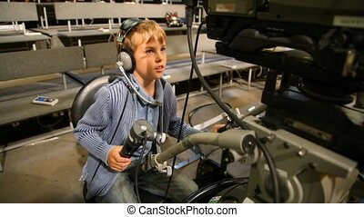 boy operating stationary camera in big TV studio with...