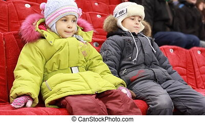 girl and boy sit on armchairs, attentively watch hockey match