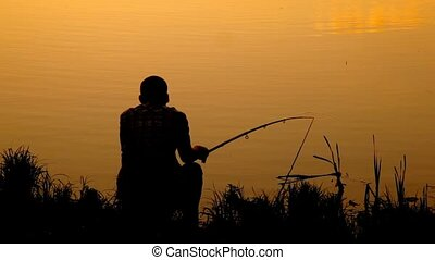 back view of man sitting with fishing rod near pond during...
