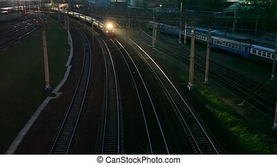 suburban electric train moving on night railway near station