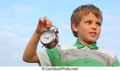 boy holding in his hand ringing alarm clock against blue sky