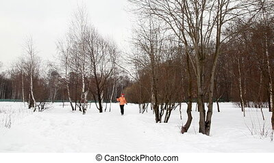 woman in winter birch forest bouncing runs up to chamber -...