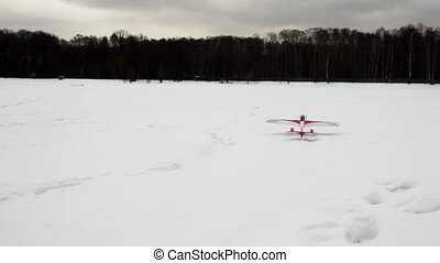 toy radio-controlled plane flies up from snow at winter wood...