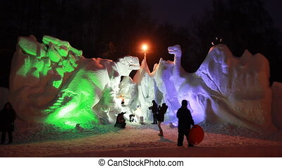 snow sculptures of dinosaurs in late evening at artificial color illumination