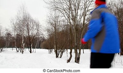 man and woman run on snow aside winter birch forest