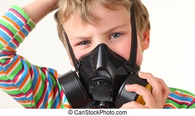 boy puts on respirator and looks at camera on white...