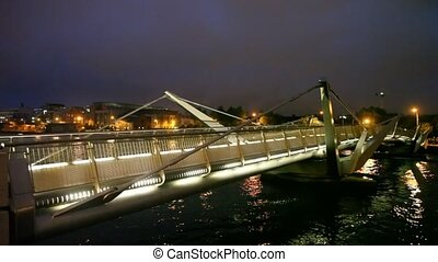 people walks on night Sean OCasey bridge in Dublin, Ireland
