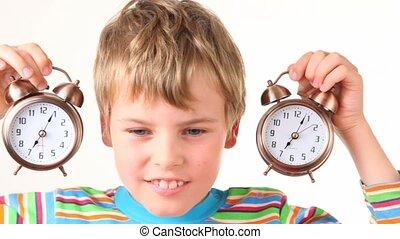 boy with pair of ringing alarm clocks near his ears on white...