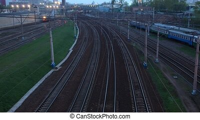 Electric trains moves on rails, springs evening. Time lapse.