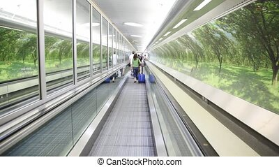 Back view of walking people with bags on escalator in London, UK.