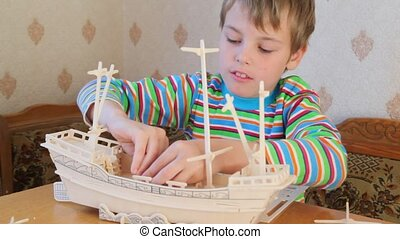 boy constructing toy model of ship - smiling happy boy...