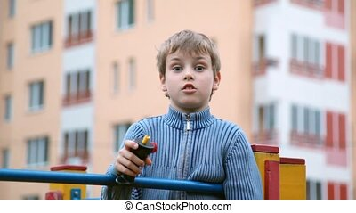 boy plays with hand gear propeller, apartment house on...