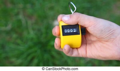 hand of boy using hand-held tally counter against grass -...