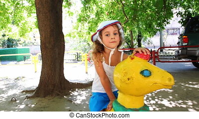 girl sits on toy horsy in middle of children's playground,...