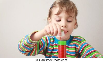 little girl blowing soap bubbles on white
