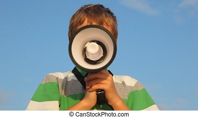 face of boy behind the megaphone against blue sky