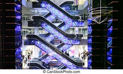 People on escalators in Evropeisky Mall in Moscow, Russia -...