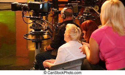 back view of spectators and cameraman in TV studio during...