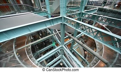 multilevel interior of factory with escalators and ladders