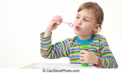 girl sitting and blowing soap bubbles