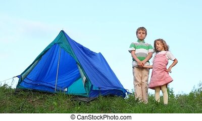 boy and little girl having joines hands stands near tent