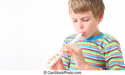 boy in shirt plays on wooden pipe - boy in multicoloured...