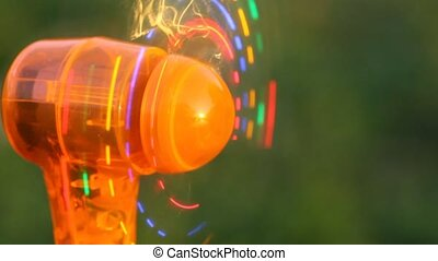 close-up shot of mini fans with LED light party on grass -...
