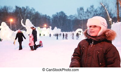 boy is telling camera on evening, behind snow sculptures of animals.