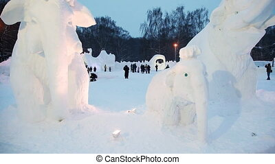 Panoramic view on snow sculptures of mammoths at winter evening on snow small town
