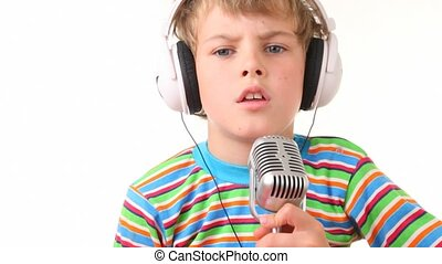boy in earphones talking through microphone on white...