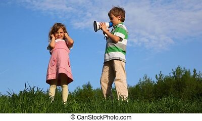 boy talking through megaphone with little girl plugging up...