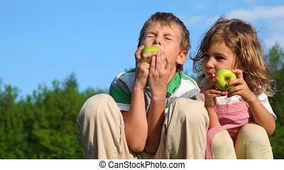 boy with girl sitting on grass and eating apples